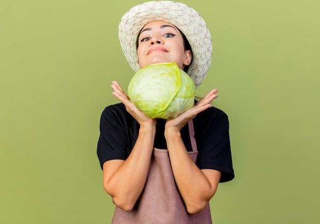 Giardiniere della giovane bella donna in grembiule e cappello che tiene il cavolo guardando davanti sorridente con la faccia felice in piedi sopra la parete verde chiaro