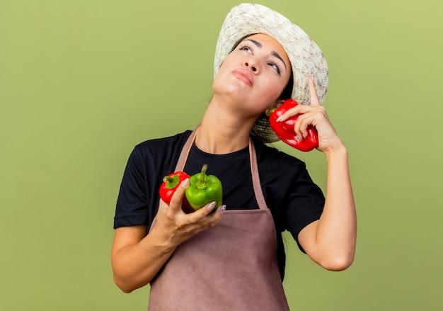 Giardiniere della giovane bella donna in grembiule e cappello che tiene i peperoni dolci variopinti che cercano in piedi perplesso sopra la parete verde chiaro