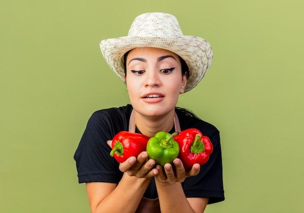 Giardiniere della giovane bella donna in grembiule e cappello che tengono i peperoni dolci variopinti che sorridono allegramente in piedi sopra la parete verde chiaro