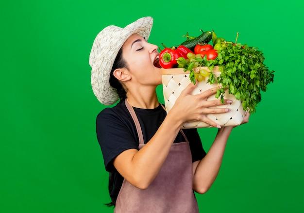 Giardiniere della giovane bella donna in grembiule e cappello che tiene cassa piena di verdure che mordono peperone rosso