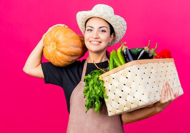 Giardiniere della giovane bella donna in grembiule e cappello che tiene cassa piena di verdure e zucca lookign alla telecamera con la faccia felice