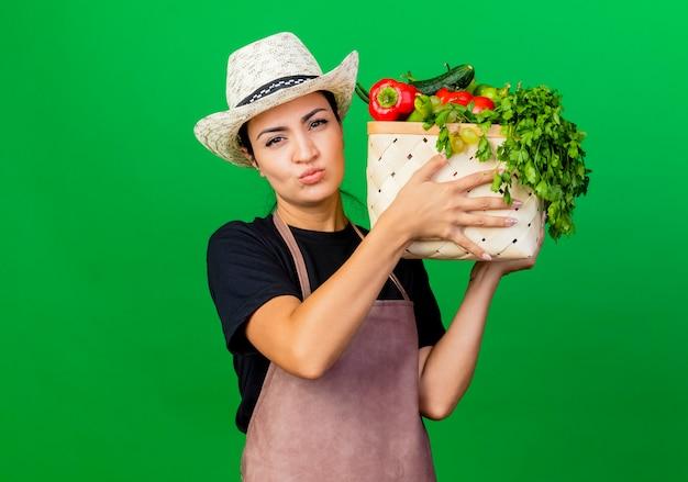 Giardiniere della giovane bella donna in grembiule e cappello che tiene cassa piena di verdure con la faccia seria