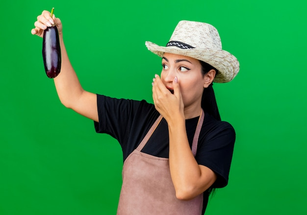 Young beautiful woman gardener in apron and hat holding eggplant looking at it being surprised and amazed standing over green wall