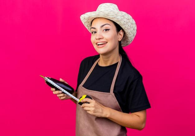 Giardiniere di giovane bella donna in grembiule e cappello che tiene melanzane e metro a nastro guardando davanti sorridente con la faccia felice in piedi sopra il muro rosa