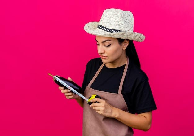 Giardiniere di giovane bella donna in grembiule e cappello che tiene melanzane e metro a nastro guardandolo con faccia seria in piedi sopra il muro rosa