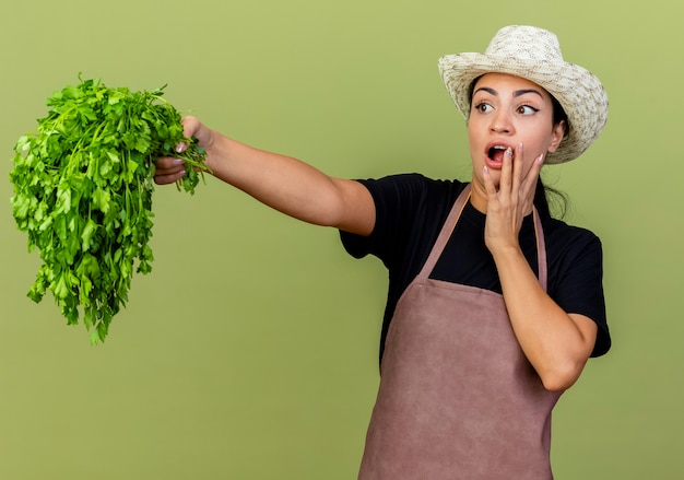Young beautiful woman gardener in apron and hat holding fresh herbs looking aside being surprised and amazed standing over light green wall