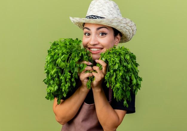Giardiniere della giovane bella donna in grembiule e cappello che tengono le erbe fresche che esaminano sorridere allegramente davanti che sta sopra la parete verde chiaro