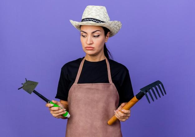 Giardiniere della giovane bella donna in grembiule e cappello che tiene attrezzatura da giardinaggio che sembra confusa e scontenta in piedi sopra la parete blu