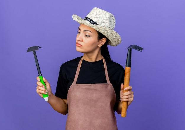 Giardiniere della giovane bella donna in grembiule e cappello che tiene attrezzatura da giardinaggio che sembra confuso cercando di fare scelta in piedi sopra la parete blu