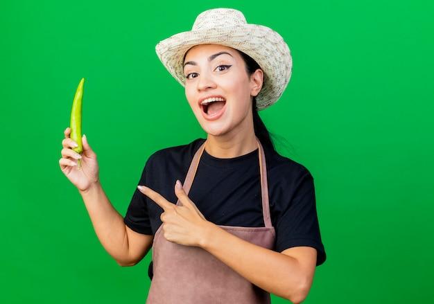 Giardiniere della giovane bella donna in grembiule e cappello che tengono il pointign del peperoncino verde con il dito sorridente che sta sopra la parete verde
