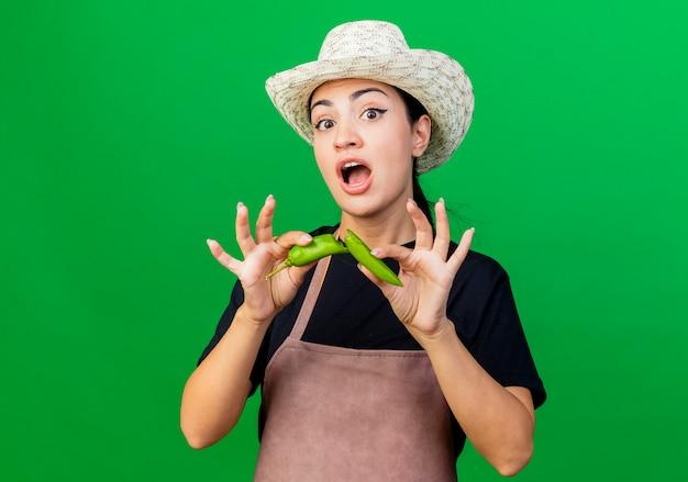 Giardiniere della giovane bella donna in grembiule e cappello che tengono il peperoncino verde sorridente sorpreso