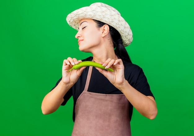 Giardiniere della giovane bella donna in grembiule e cappello che tengono peperoncino verde con gli occhi chiusi