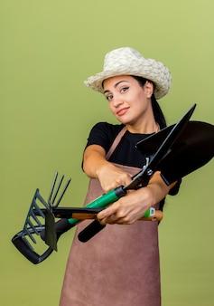 Giardiniere della giovane bella donna in grembiule e cappello che tiene tagliasiepi e mattock guardando davanti sorridente in piedi sopra il muro verde chiaro