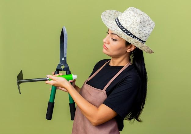 Giardiniere di giovane bella donna in grembiule e cappello che tiene tagliasiepi e mattock guardandoli con faccia seria in piedi sopra la parete verde chiaro