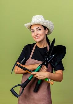 Giardiniere di giovane bella donna in grembiule e cappello che tiene tagliasiepi e vanga e pala sorridente con la faccia felice in piedi sopra la parete verde chiaro