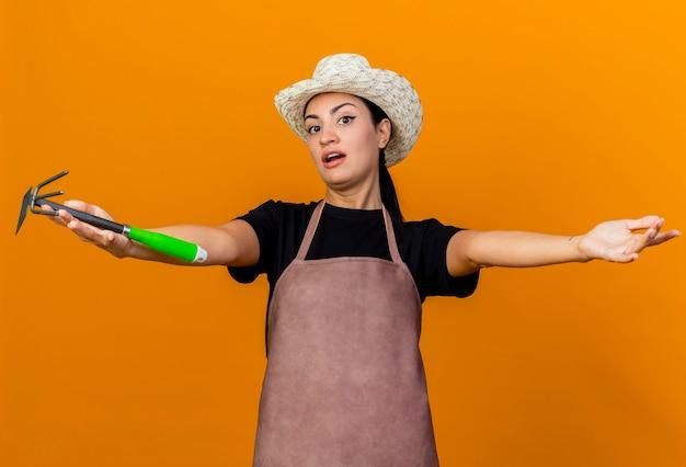 Giardiniere della giovane bella donna in grembiule e cappello che tiene mattock guardando le mani di ampia apertura anteriori in piedi sopra la parete arancione
