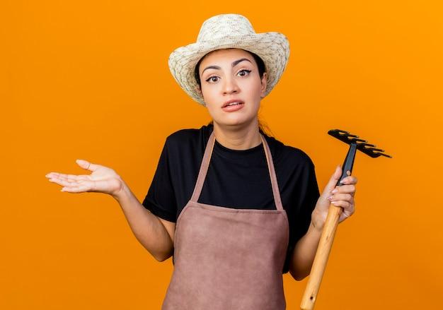 Giardiniere della giovane bella donna in grembiule e cappello che tiene mini rastrello che guarda in piedi confuso davanti sopra la parete arancione