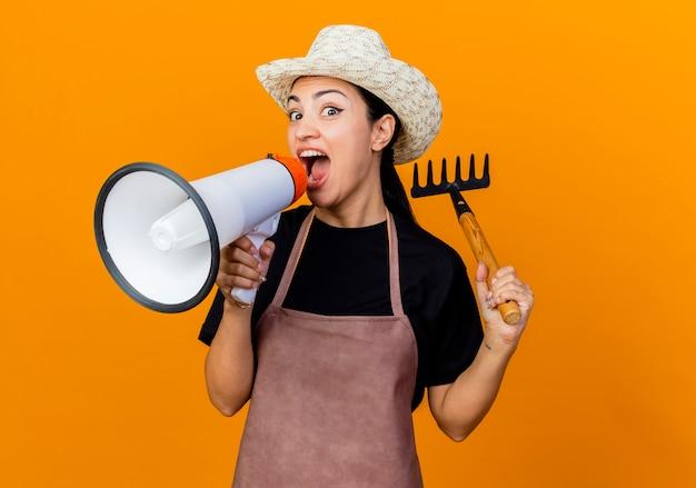 Giardiniere di giovane bella donna in grembiule e cappello che tiene mini rastrello guardando davanti gridando al megafono in piedi sopra la parete arancione