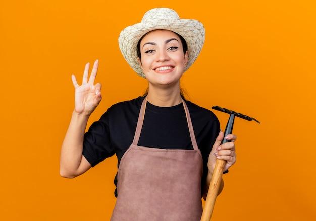 Giardiniere della giovane bella donna in grembiule e cappello che tiene mini rastrello guardando davanti sorridente che mostra segno giusto in piedi sopra la parete arancione