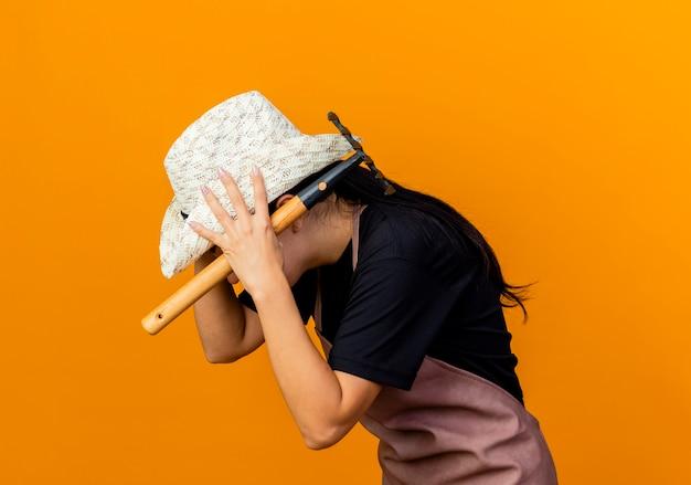 Giardiniere della giovane bella donna in grembiule e cappello che tiene mini rastrello che sembra spaventato mentre tiene la sua testa che si leva in piedi sopra la parete arancione