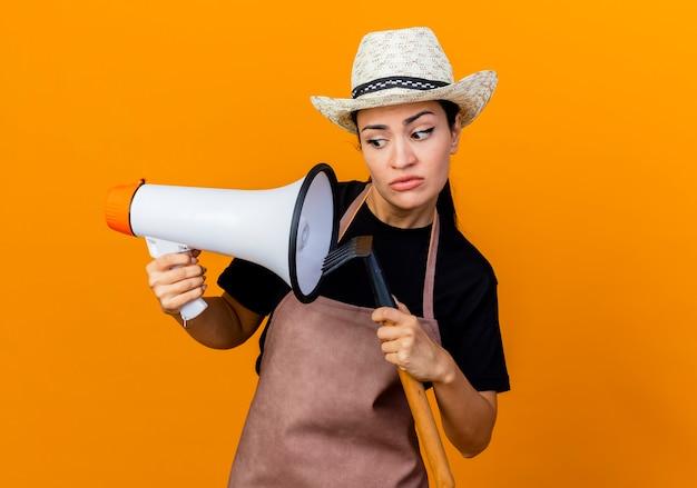 Giardiniere della giovane bella donna in grembiule e cappello che tiene mini rastrello e megafono che sembra confuso in piedi sopra la parete arancione