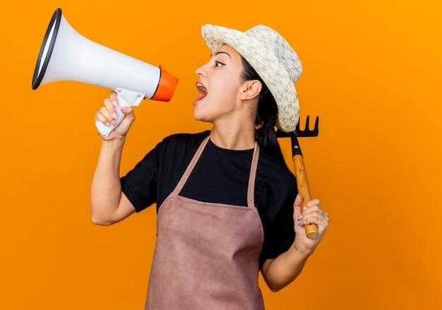 Giardiniere della giovane bella donna in grembiule e cappello che tiene mini rastrello che grida al megafono che sta sopra la parete arancione