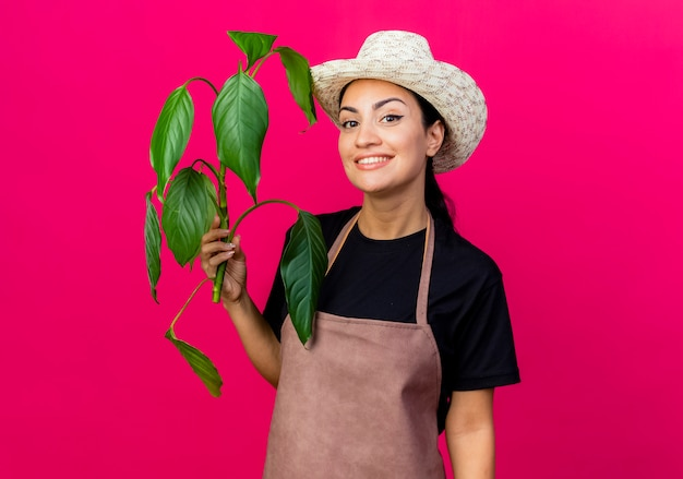 Young beautiful woman gardener in apron and hat holding plant looking at front smiling with happy face standing over pink wall