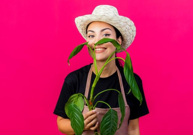 Giovane bella donna giardiniere in grembiule e cappello che tiene pianta che sembra sorridente con la faccia felice in piedi