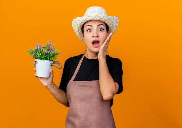 Young beautiful woman gardener in apron and hat holding potted plant looking at front being surprised and amazed standing over orange wall