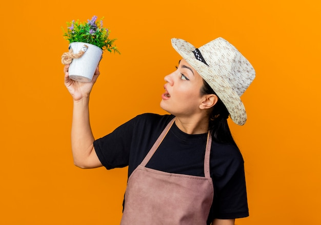Young beautiful woman gardener in apron and hat holding potted plant looking at it being surprised and amazed standing over orange wall