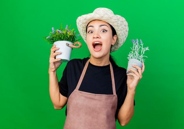 Giardiniere della giovane bella donna in grembiule e cappello che tengono le piante in vaso che sono sorpresi
