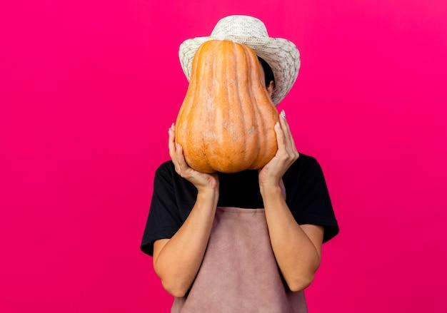 Giardiniere della giovane bella donna in grembiule e cappello che tiene la zucca che nasconde il suo fronte che sta sopra il muro rosa