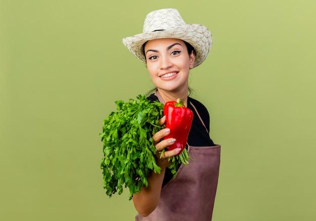 Giardiniere della giovane bella donna in grembiule e cappello che tengono il peperone dolce rosso e le erbe fresche che sorridono allegramente in piedi sopra la parete verde chiaro