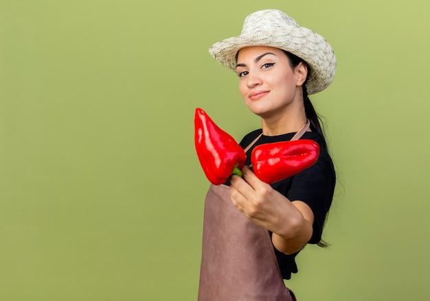 Giardiniere di giovane bella donna in grembiule e cappello che tiene peperoni rossi guardando davanti sorridente allegramente in piedi sopra il muro verde chiaro