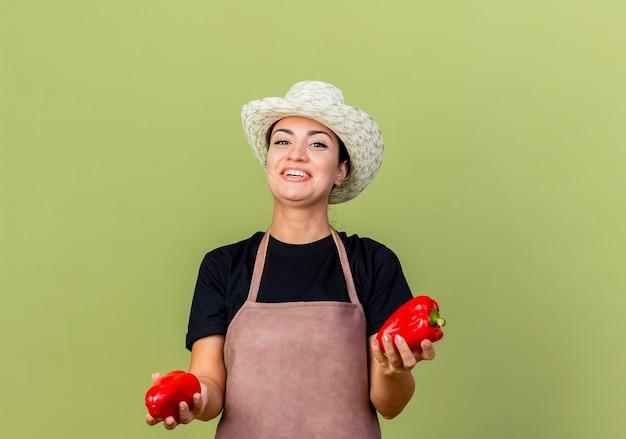Giardiniere della giovane bella donna in grembiule e cappello che tengono i peperoni dolci rossi che sorridono allegramente in piedi sopra la parete verde chiaro