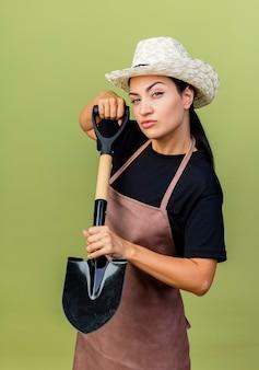 Giardiniere della giovane bella donna in grembiule e cappello che tiene la pala guardando la parte anteriore con la faccia seria in piedi sopra la parete verde chiaro