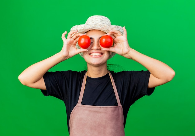 Giardiniere della giovane bella donna in grembiule e cappello che tengono i pomodori che coprono gli occhi con loro sorridendo
