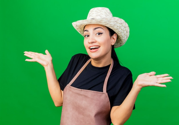 Young beautiful woman gardener in apron and hat smiling confused spreading arms to the sides