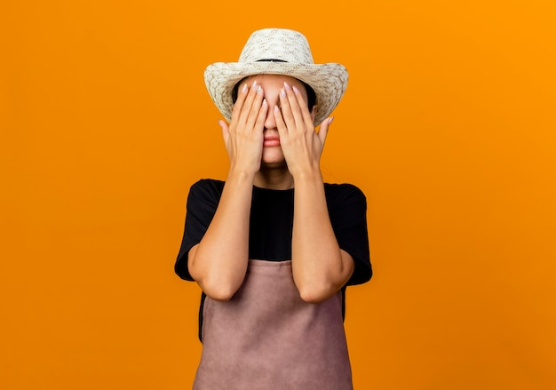 앞치마와 모자 오렌지 벽 위에 서 손으로 눈을 덮고 젊은 아름 다운 여자 정원사
