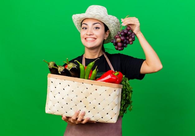 エプロンと帽子の若い美しい女性の庭師は、緑の壁の上に幸せで前向きに立っている野菜とブドウでいっぱいのバスケットを保持しています