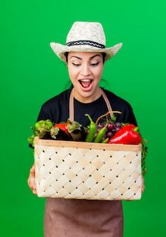 Молодая красивая женщина-садовник в фартуке и шляпе держит корзину с овощами, глядя на нее, улыбаясь, удивившись, стоя у зеленой стены