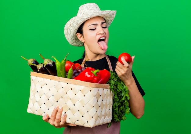 緑の壁の上に立っている嫌な表情でトマトを見ている野菜でいっぱいのバスケットを保持しているエプロンと帽子の若い美しい女性の庭師