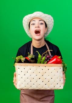 Молодая красивая женщина-садовник в фартуке и шляпе держит корзину, полную овощей, кричит со счастливым лицом, стоя над зеленой стеной