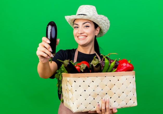 Молодая красивая женщина-садовник в фартуке и шляпе держит корзину, полную овощей, показывая баклажаны, улыбаясь счастливым лицом, стоящим над зеленой стеной