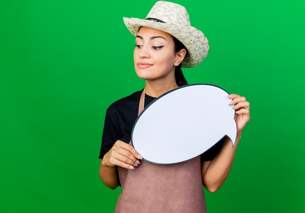 緑の壁の上に立っている顔に笑顔で脇を見て空白の吹き出し看板を保持しているエプロンと帽子の若い美しい女性の庭師