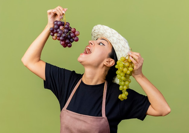 エプロンと帽子の若い美しい女性の庭師は、薄緑色の壁の上に立ってブドウを食べに行くブドウの広い開口部の房を保持