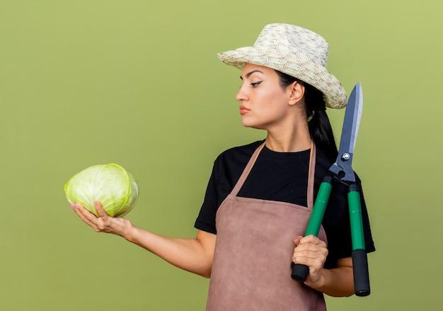 薄緑色の壁の上に立っている真面目な顔でキャベツを見ているキャベツとヘッジクリッパーを保持しているエプロンと帽子の若い美しい女性の庭師