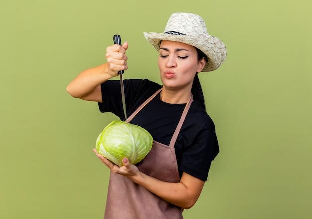薄緑色の壁の上に立って混乱しているように見えるキャベツと包丁を保持しているエプロンと帽子の若い美しい女性の庭師