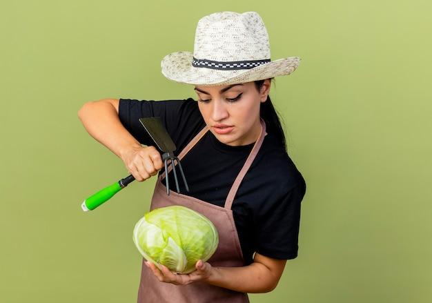 薄緑色の壁の上に立っている真面目な顔でそれを見てキャベツとマトックを保持しているエプロンと帽子の若い美しい女性の庭師