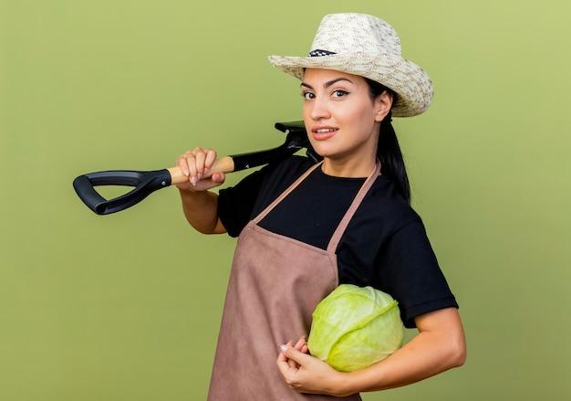 薄緑色の壁の上に立って笑顔の正面を見てキャベツとシャベルを保持しているエプロンと帽子の若い美しい女性の庭師